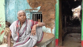 Neelamma, 80, keeps a watch on monkeys and strays in front of her damaged house in Kakkaragol of Koppal district. Pic: Savita Hiremath