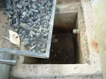 A bucket is placed in this pit below the small pipe jutting out to collect the leacheate that flows out.